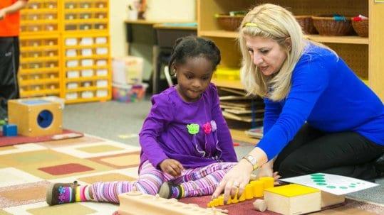 Teacher showing little girl the Montessori curriculum.