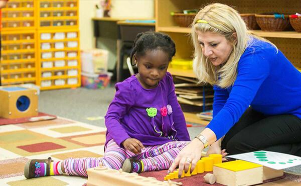 Teacher showing child part of the Montessori curriculum.